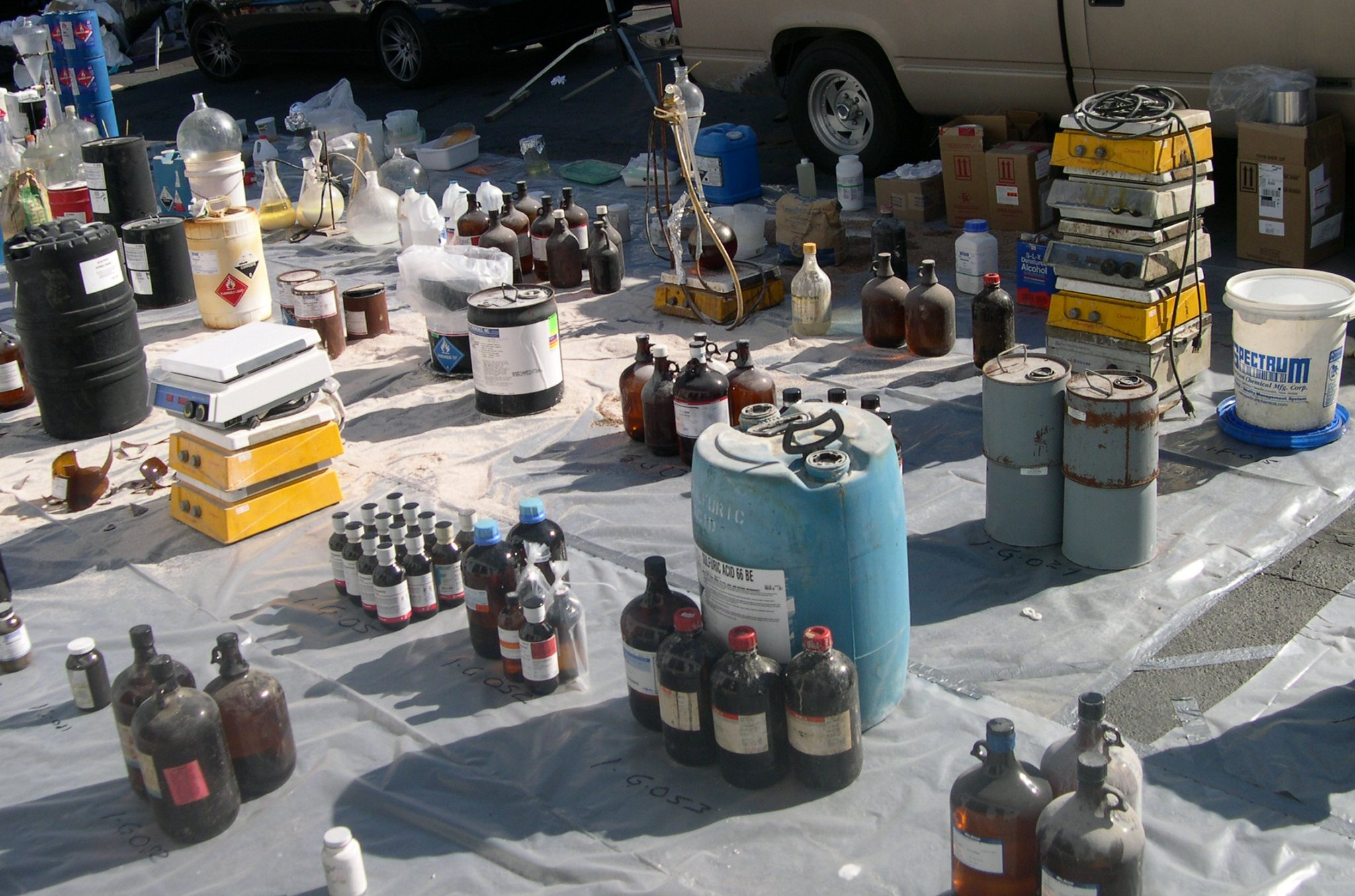 Various recovered hazardous waste items laid out upon a large tarp