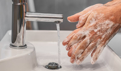 Person washing their hands with soap and water