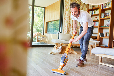 Man vacuuming a floor in a home